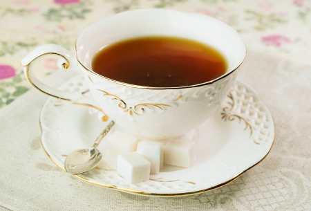 Gourmet tea cup with sugar cubes on a linen napkin Stock Photo