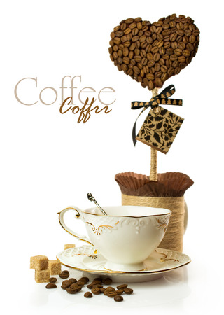 Coffee cup with hand made topiary of coffee beans isolated on white photo
