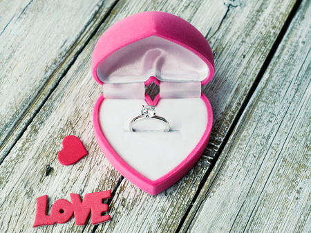 Ring with diamond in heart shaped box close-up photo