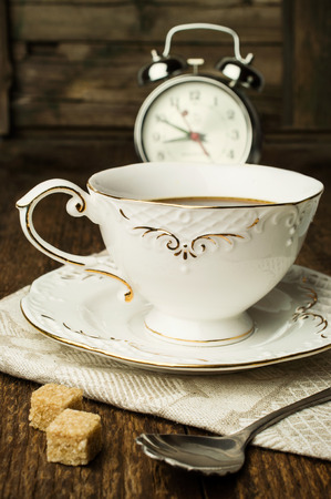 Morning tea .Exquisite cup of tea and a classic alarm clock on wooden background photo
