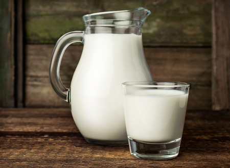 milk jugs: fresh milk in glass jug and glass on wooden background