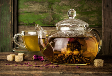 Blooming green tea in glass teapot on a wooden table photo