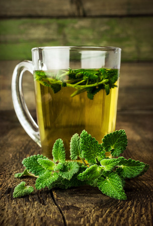 mint tea in glass cup with fresh leaves closeup photo