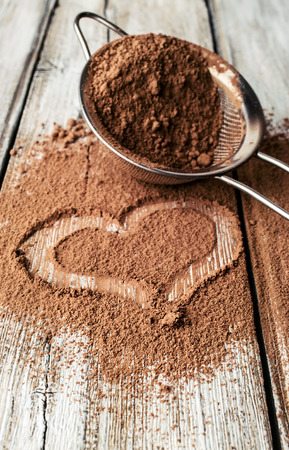 heart painted on cocoa powder and sieve photo