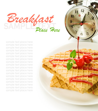 sou: Still life breakfast: waffles with cherry topping and alarm clock isolated on white Stock Photo