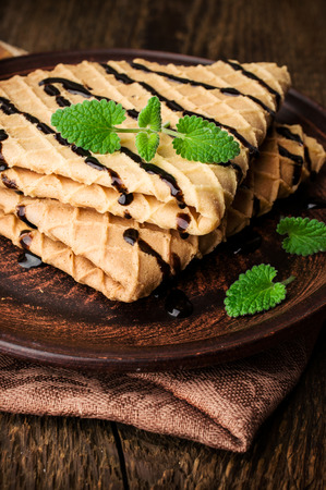 sou: waffles with chocolate topping and mint on a wooden