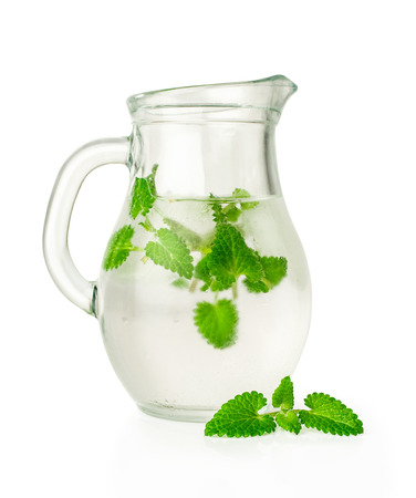 water with ice and mint in a glass jug isolated on white