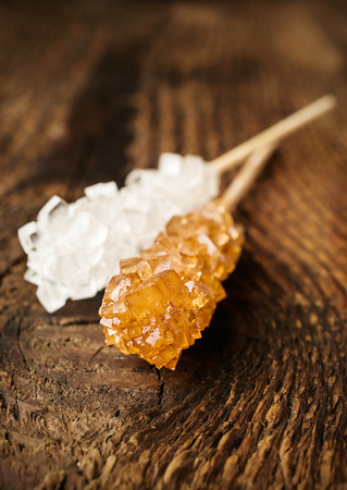 cane sugar on a stick on a wooden background photo