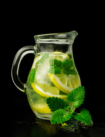 lemonade with ice and mint in a glass pitcher isolated on white photo