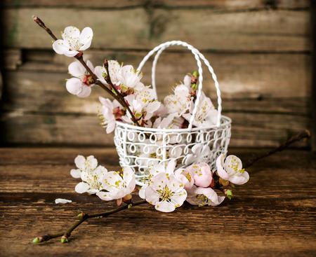 梅の花の木製の背景に金属のバスケットに