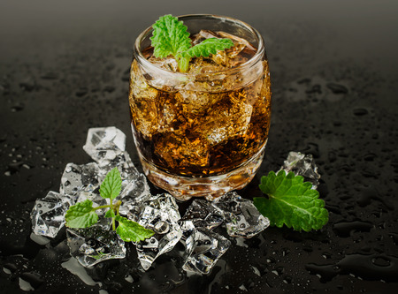 whiskey with ice and mint on black background photo