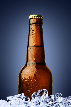bottle of beer with ice on blue background photo