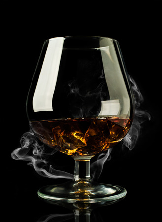 whiskey in glass with ice on a black background with smoke photo