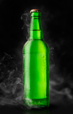 green bottle of chilled beer on a black background photo