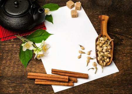 Asian tea recipe .blank sheet of paper , teapot , jasmine and cinnamon on wooden background photo