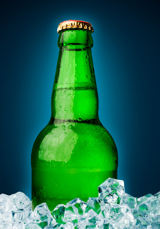 beer in a green bottle with ice cubes photo