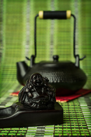 stand teapot: Asian tea. Black clay teapot and incense stand closeup on bamboo background