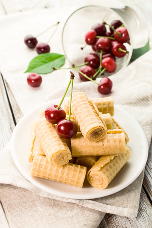 sou: Sweet wafer rolls with fresh  cherries on table