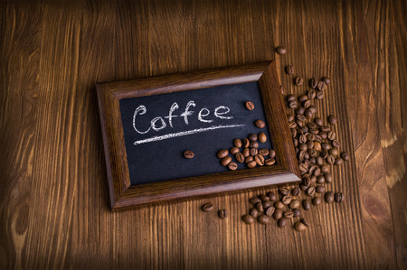 slate with coffee beans on wooden background photo