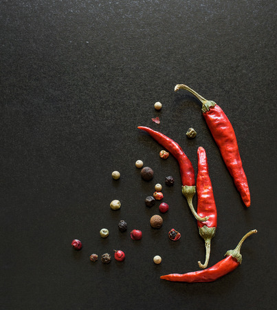 shiny black: Spices on a blackboard  Chili pepper , bay leaves and allspice Stock Photo