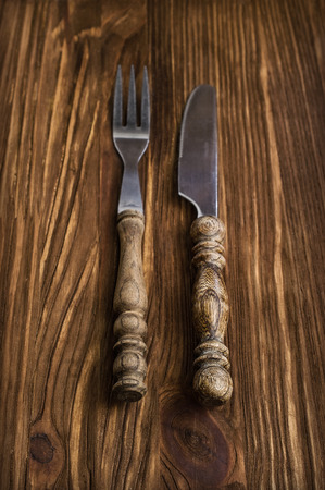 grunge silverware: cutlery on a wooden background in rustic style