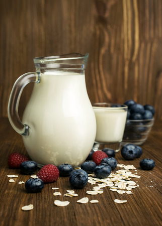 Ingredients for breakfast : milk, cereal , blueberries and raspberries on woooden Stock Photo
