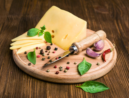 cheese, spices and a knife on a wooden background photo