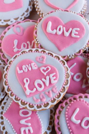 background with homemade cookies with frosting in the shape of hearts and the words love photo