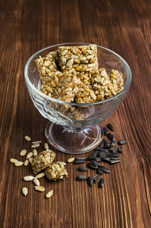 Honey bars with sunflower seeds in glass on wooden photo