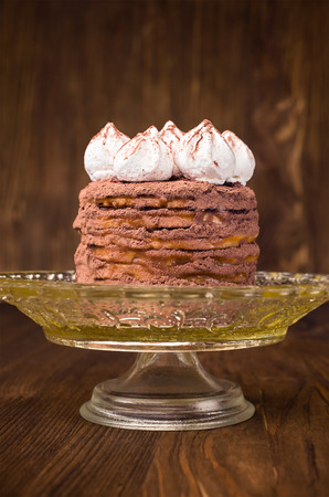 layer cake with cocoa on a stand on a wooden background photo