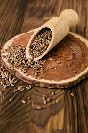 flax seeds: Flax seeds  in wooden scoop on a cut down a tree