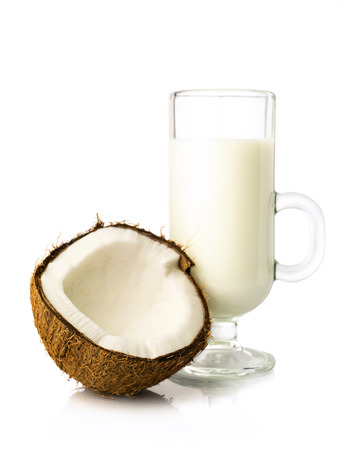 half of fresh coconut and coconut milk in a glass isolated on white