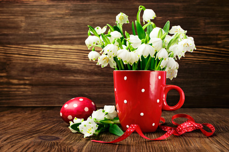 pattern pois: Snowdrops in una tazza con motivo a pois e uova dipinte su uno sfondo in legno