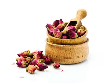 Toppen van de gedroogde rozen voor thee in een houten kom geïsoleerd over white Stockfoto