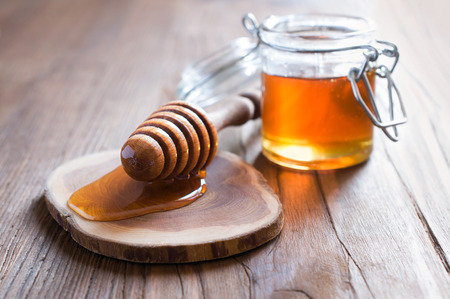 honey pot: Honey in jur with wooden dipper in rustic style