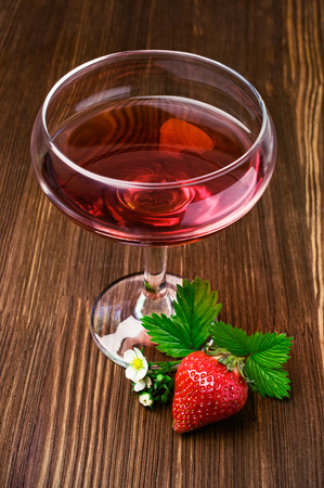 tipple: Red beverage with strawberry on wooden background