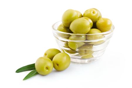 hoja de olivo: aceituna verde en un recipiente de vidrio aislado más de blanco Foto de archivo
