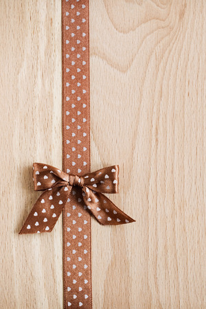paper board: wooden background with polka dot ribbon and bow
