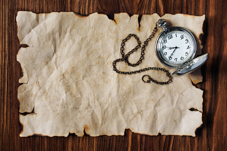 nautic: Sheet of ancient parchment or old paper and vintage pocket watch on wooden background Stock Photo
