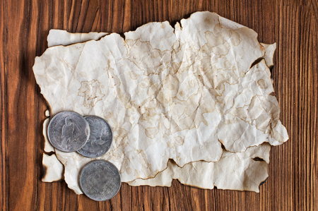 monet: Old paper and silver coins on a wooden background Stock Photo