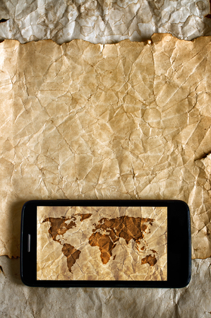 ancient telephone: Old map and smartphone. Travel concept and background Stock Photo