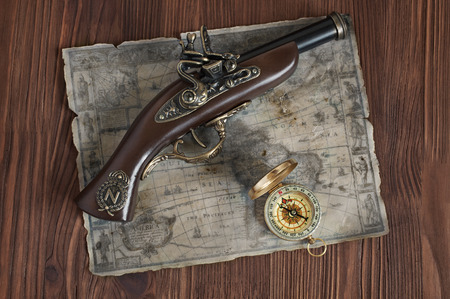 flint gun: Pirate background. The old musket, map and compass on a wooden background