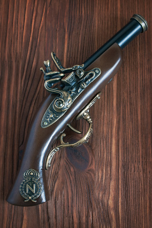 musket: The old musket on a wooden background