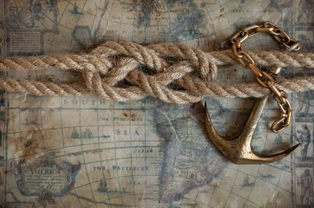 Nudo marinero y latón de anclaje se encuentran en el fondo de los mapas antiguos Foto de archivo