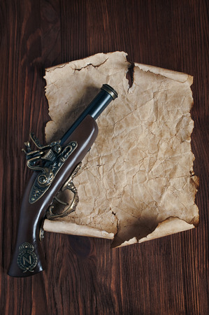 musket: Retro pistol or musket and parchment on a wooden table