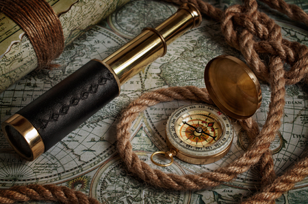 Nautical background with a navigation tools: telescope, compass and old maps