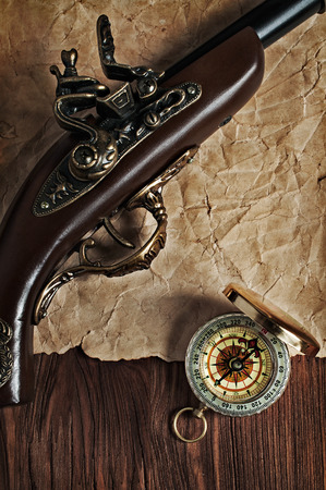 flint gun: Pirate  background. Ancient pistol and brass compass lying on old paper texture