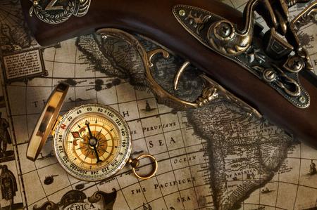 flint gun: Pirate background. Ancient map and antique handgun and brass compass.
