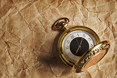 antique paper: Retro gold pocket watch on old paper texture Stock Photo