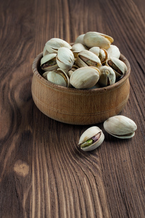 rustic food: Pistachios in a wooden bowl. Food in a rustic style.